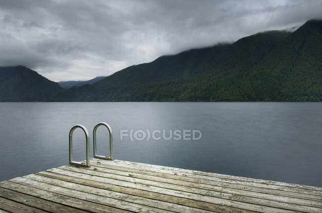 Ladder on wooden pier at still remote lake — Stock Photo