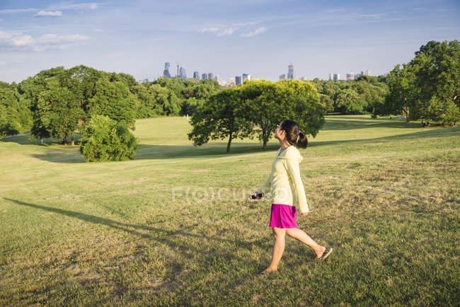 Donna asiatica che cammina nel parco urbano con grattacieli in lontananza, Philadelphia, USA — Foto stock