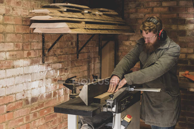 Bearded man standing in workshop, wearing ear protectors, working on piece of wood. — Stock Photo