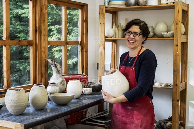 Женщина в красном фартуке стоит в мастерской, держит керамическую вазу и улыбается в камеру . — стоковое фото