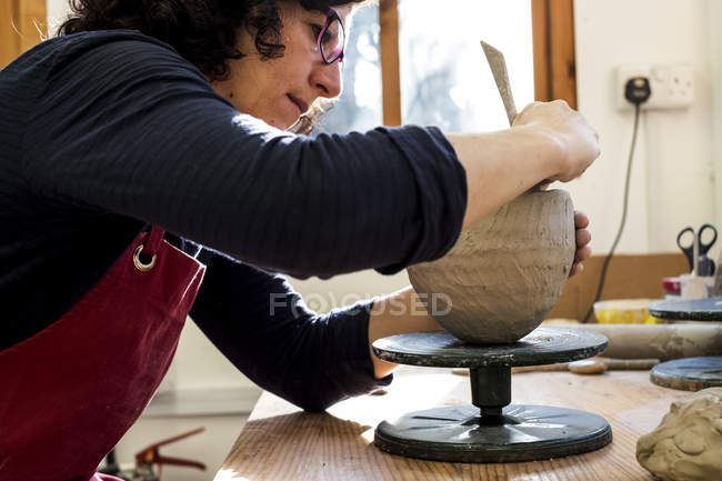 Woman in red apron sitting in ceramics workshop and working on clay vase. — Stock Photo
