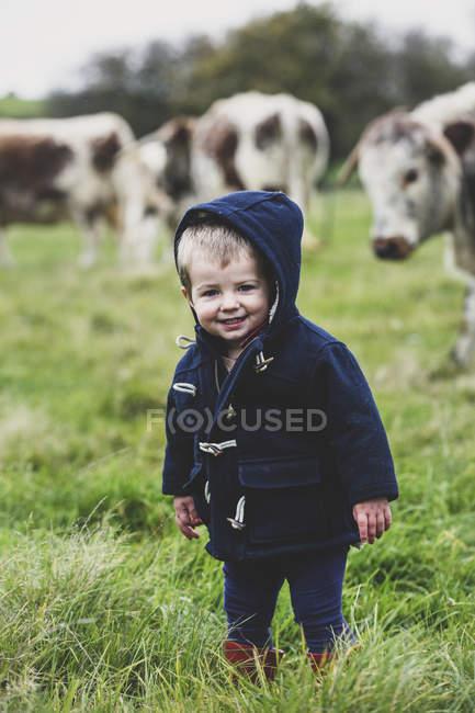 Giovane ragazzo in piedi sul pascolo con le mucche Longhorn inglesi sullo sfondo . — Foto stock