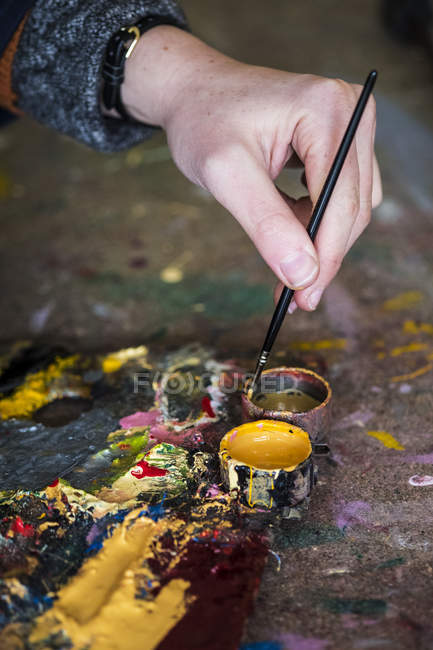Close-up of female hand dipping paintbrush into small pot of yellow oil paint. — Stock Photo