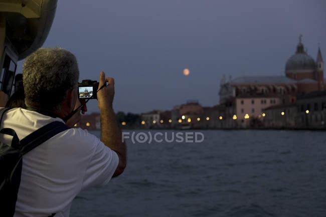 Vista traseira do turista masculino tirando fotos de Canale Grande em Veneza, Veneto, Itália à noite . — Fotografia de Stock