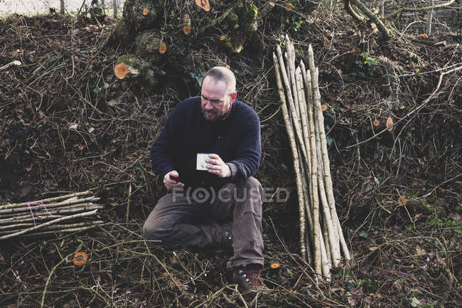 Bearded man sitting on ground next to bunch of wooden stakes, holding mug, checking mobile phone. — Stock Photo