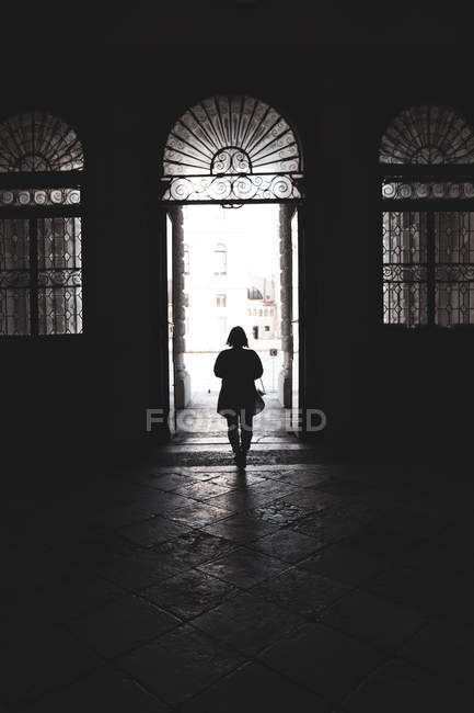 Silhouette of woman walking through arched doorway in Venice, Veneto, Italy. — Stock Photo