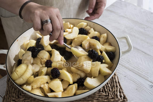 Close-up of hands of woman placing apples and blackberries in round baking tin. — Stock Photo