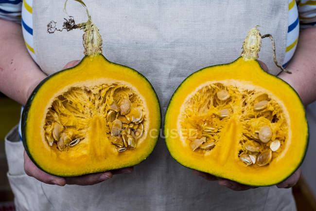 Close-up de pessoa segurando abóbora com carne de laranja cortada ao meio . — Fotografia de Stock