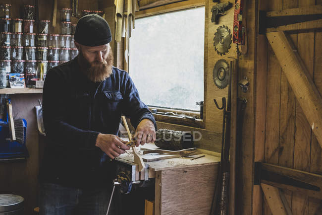Bearded man in black beanie standing at workbench in workshop, working on piece of wood. — Stock Photo