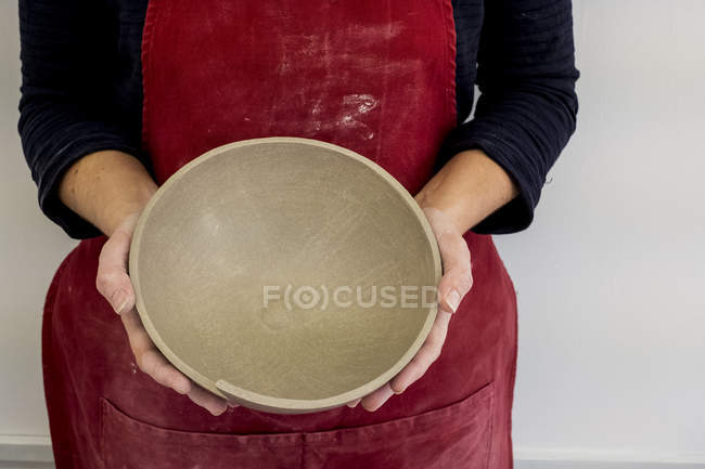 Midsection of ceramic artist in red apron working on small clay bowl. — Stock Photo