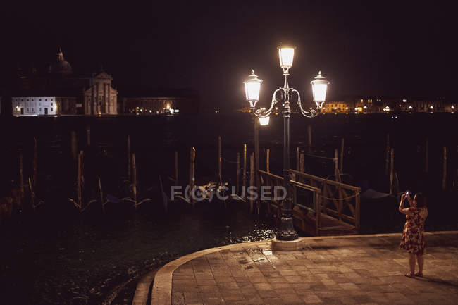 Female tourist taking picture of streetlight by lagoon in Venice, Veneto, Italy at night. — Photo de stock