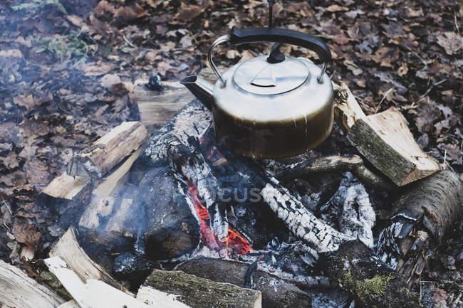 Grand angle gros plan de bouilloire métallique suspendue au-dessus du feu de camp . — Photo de stock