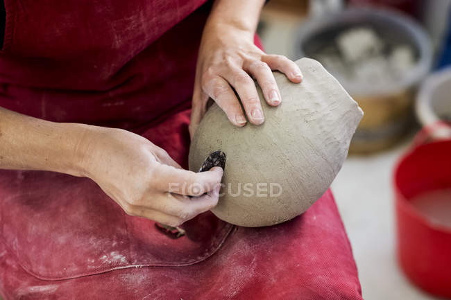 Hands of ceramic artist in red apron sitting in workshop, working on clay vase. — Foto stock