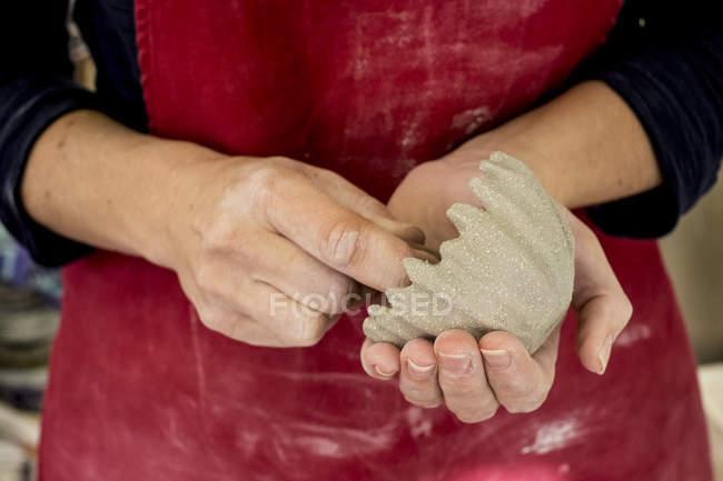 Средняя часть керамического художника в красном фартуке работает на небольшой глиняной чаше . — стоковое фото