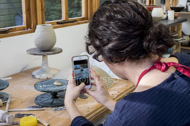 Over the shoulder view of woman sitting in ceramics workshop and checking mobile phone. — Stock Photo
