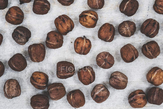 High angle close-up of fresh walnuts on grey background. — Stock Photo