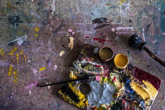 Alto ângulo close-up de paleta, tintas a óleo e pincel na oficina . — Fotografia de Stock