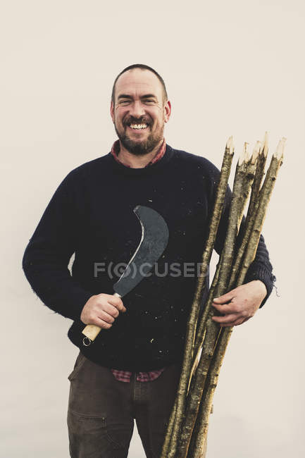 Bearded man holding bill hook and bunch of wooden stakes for traditional hedge laying, smiling in camera. — Stock Photo