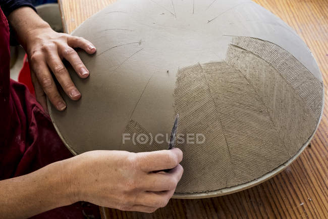 Close-up of ceramic artist working on clay bowl, applying pattern with hand tool. — Stock Photo