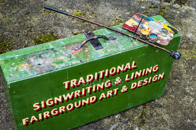 High angle view of painting materials on green metal toolbox of traditional sign-writer. — Stock Photo