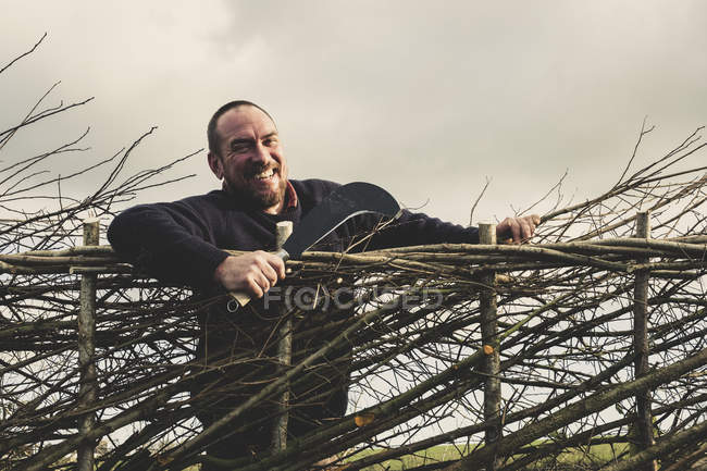 Smiling bearded man holding bill hook standing next to newly built traditional hedge. — Stock Photo