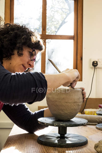 Woman sitting in ceramics workshop and working on clay vase. — Stock Photo