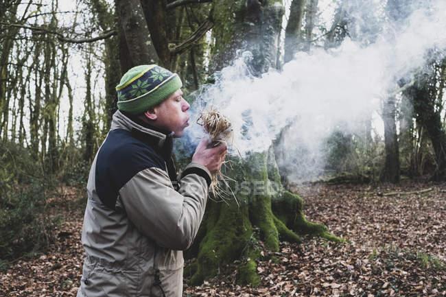 Mann steht im Wald und pustet auf Strohballen und entzündet Feuer. — Stockfoto