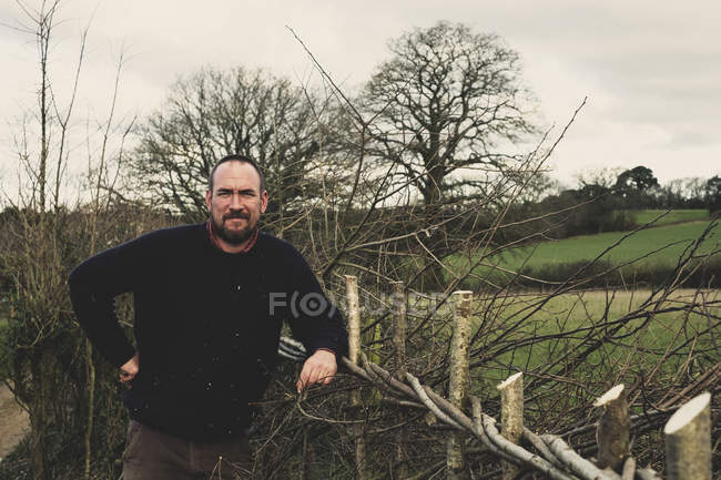 Bearded man standing next to newly built traditional hedge, smiling in camera. — Stock Photo