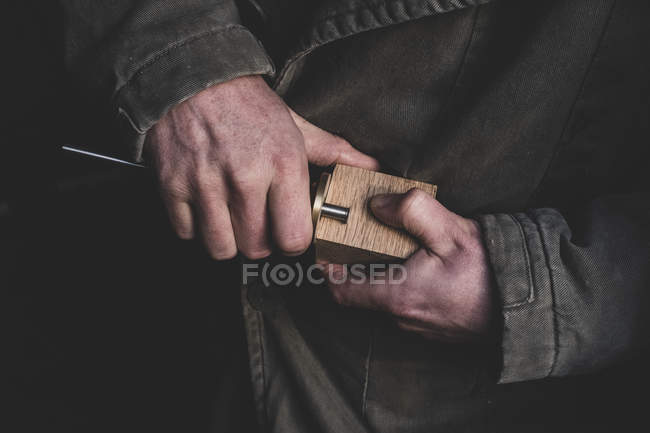 High angle close-up of man fitting metal part onto wooden block. — Stock Photo