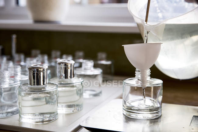 Close up of person pouring liquid for scent diffuser into glass bottle. — стокове фото