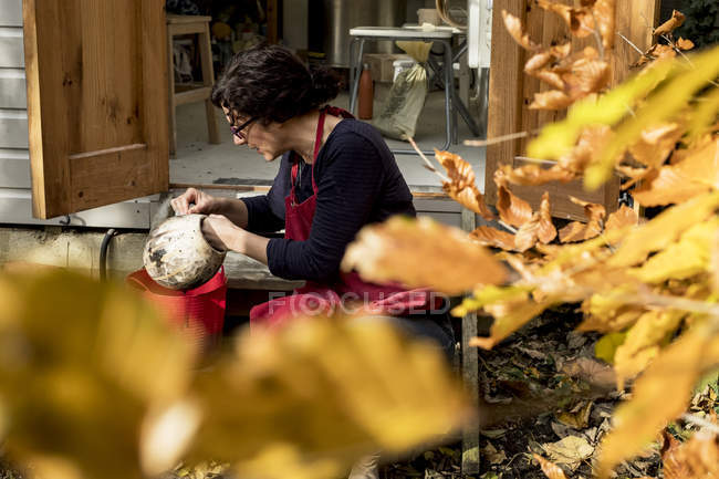 Woman in red apron sitting outside ceramics workshop and holding vase. — Stock Photo