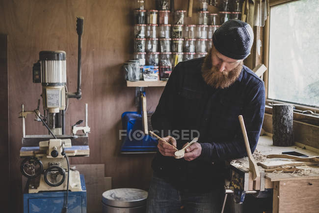 Bearded man wearing black beanie standing at workbench in workshop, examining piece of wood. — Stock Photo