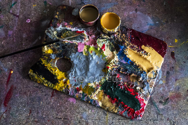High angle close-up of palette, oil paints and paintbrush in workshop. — Stock Photo