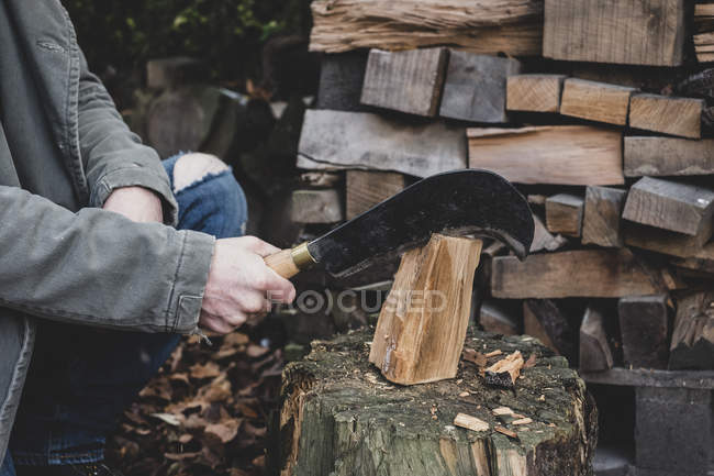 Close-up of man using machete cleaver on chopping block, splitting piece of wood. — Stock Photo