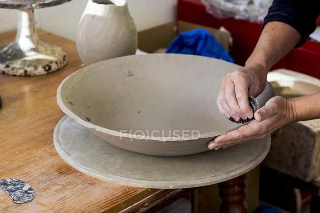 Primo piano dell'artista ceramico in laboratorio a lavorare su ciotola di argilla. — Foto stock
