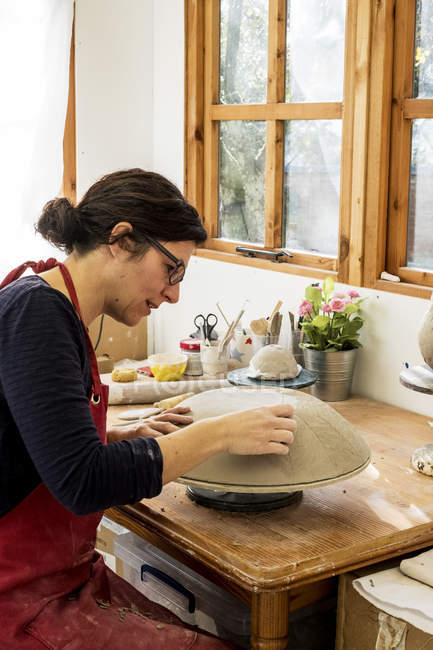 Woman in red apron sitting in ceramics workshop, working on clay bowl. — Stock Photo