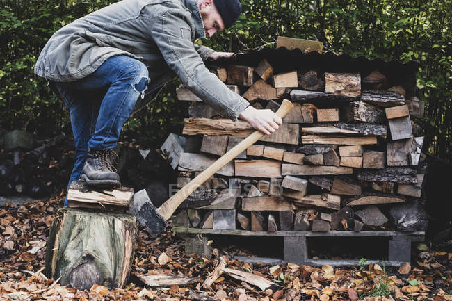 Bearded man in black beanie and parka standing in garden in autumn, using axe to chopping piece of wood on chopping block. — Stock Photo