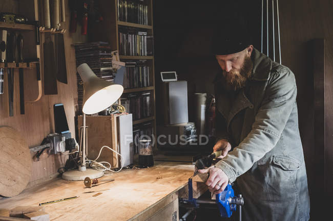 Bearded man wearing black beanie standing at workbench in workshop, sawing piece of wood. — Stock Photo