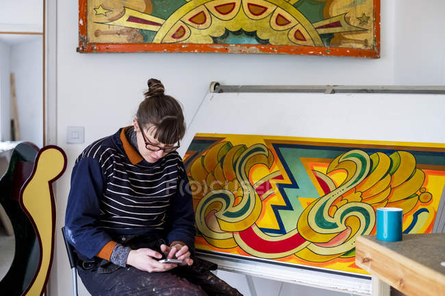 Female artist  sitting by drawing in progress at drawing table in workshop and checking mobile phone. — Stock Photo