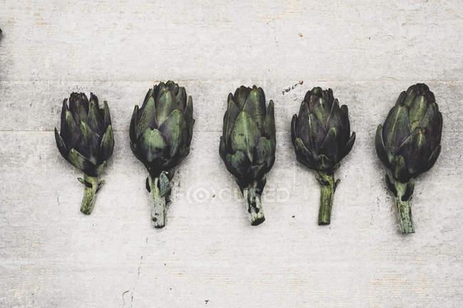 Close-up of fresh artichokes on grey background. — Stock Photo