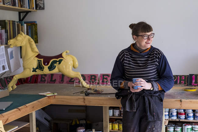 Woman sitting in workshop next to traditional wooden carousel galloper horse from merry-go-round. — Stock Photo