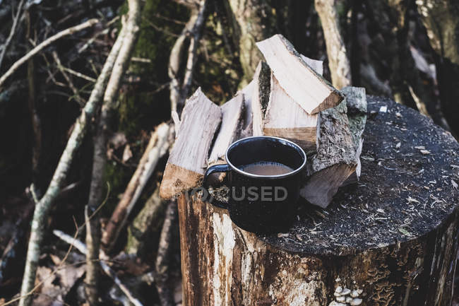 High angle view of mug of tea and wooden logs on chopping block. — Stock Photo