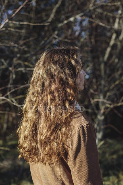 Rear view of teenage girl with long wavy brown hair standing outdoors — Stock Photo