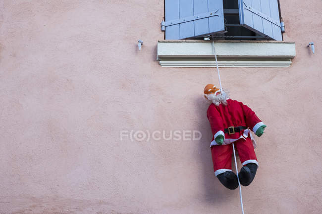 Santa Clause figure hanging on rope from window of house with pink facade. — Stock Photo