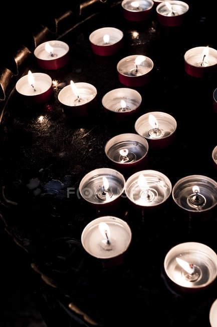 Primer plano de ángulo alto de velas de luz de té encendidas en la bandeja en la iglesia . - foto de stock