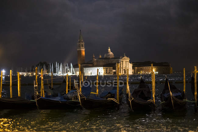 Illuminated gondolas moored in Canale Grande in Venice, Italy, at night and view across water lagoon — Stock Photo