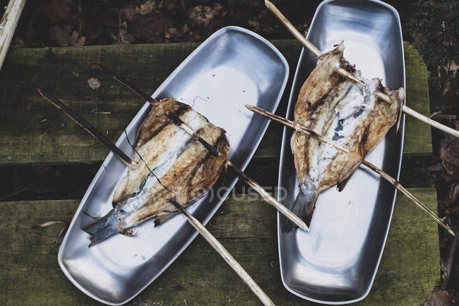 High angle close-up of grilled fish on wooden skewers on metal plates outdoors — Foto stock