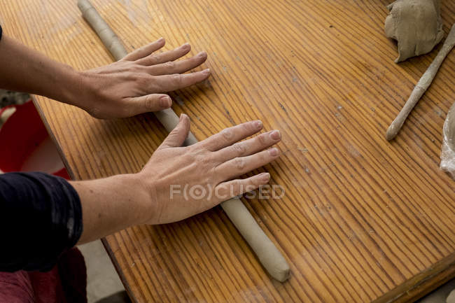 Hands of ceramic artist in workshop rolling piece of clay on wooden table. — Stock Photo