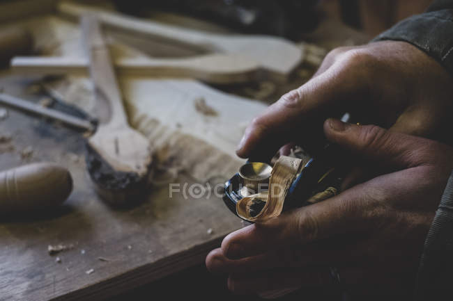 High angle close-up of man using plane on piece of wood. — Stock Photo