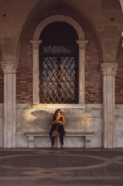 Femme assise sur un banc sous une fenêtre cintrée à Venise, Vénétie, Italie . — Photo de stock